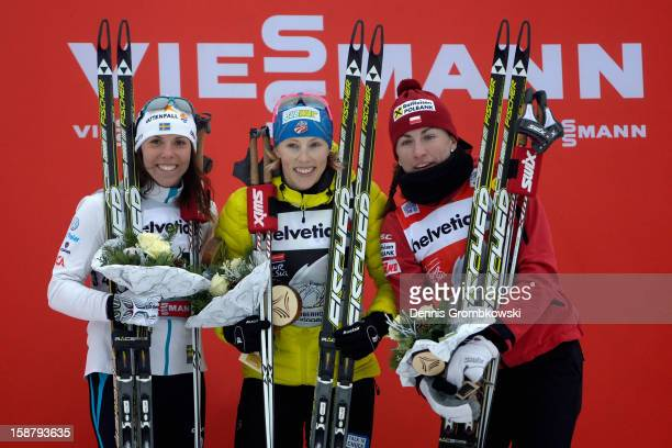 Charlotte Kalla of Sweden Kikkan Randall of the United States and Justyna Kowalczyk of Poland celebrate at the podium after the Women's 31km Free...