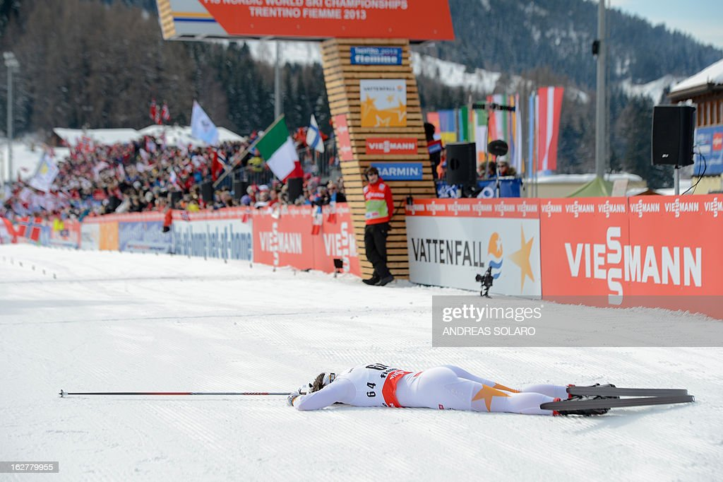 Charlotte Kalla of Sweden lies down inside the finish area on February 26, 2013, at the end of the Women's Cross Country skiing 10 Km Free Individual of the FIS Nordic World Ski Championships at Val Di Fiemme Cross Country stadium in Cavalese, north Italy . AFP PHOTO / ANDREAS SOLARO