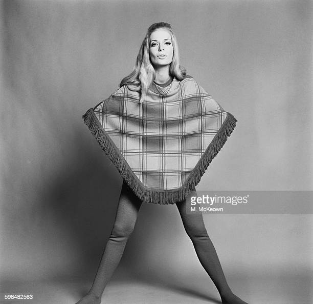 Charlotte Louise models a pink and purple checked woollen poncho over purple tights UK 15th September 1967