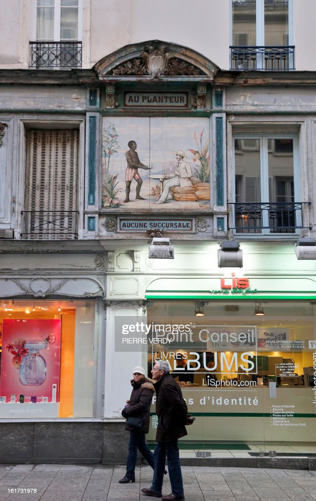 Charlotte PLANTIVE People walk by a colonialist fresco made with ceramics taken on February 15, 2013 in central Paris.