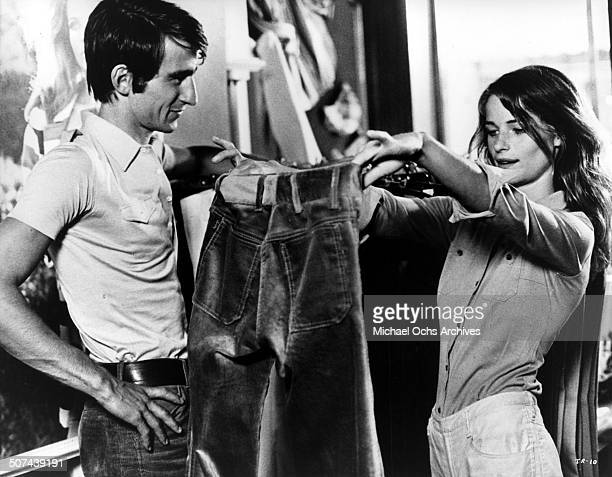 Charlotte Rampling checks a pair of blue jeans for Sam Waterston in a scene from the movie 'Three' circa 1967