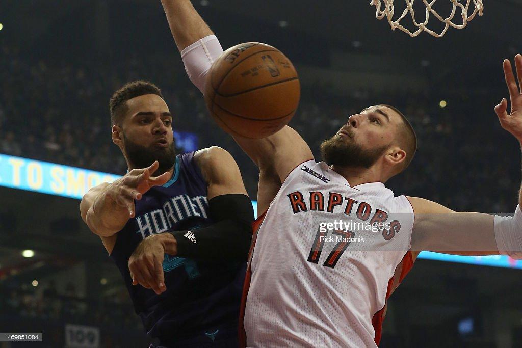 TORONTO APRIL 15 Charlotte's Jeff Taylor dishes off under the hoop as Raptors Jonas Valanciunas plays defence Toronto Raptors vs Charlotte Hornets...