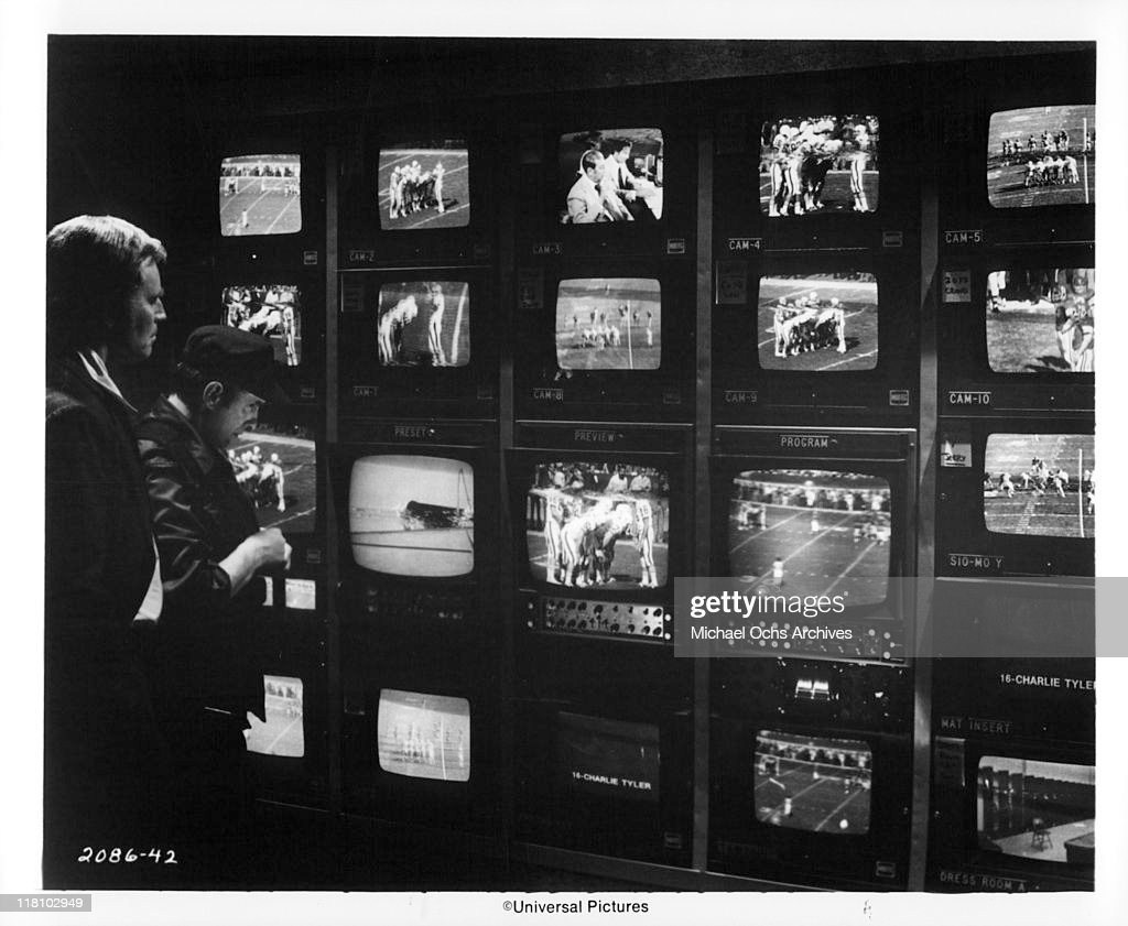 Charlton Heston watches network television monitors which spot a hidden sniper at the Los Angeles Coliseum in a scene from the film 'TwoMinute...