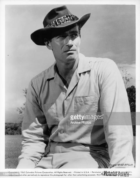Charlton Heston wearing a hat and a linen long sleeve shirt in a scene from the film 'Diamond Head' 1962