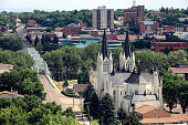 High angle view of downtown Medicine Hat Alberta. St Patricks Church in foreground. City Hall behind and over bridge. Old historic and saved brick buildings. Several churches in photo.