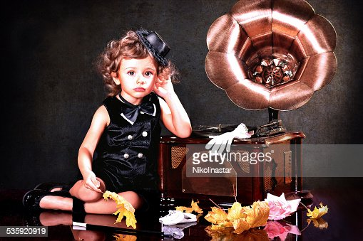 Charming baby listening to music : Stock Photo