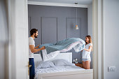 Charming beautiful couple in love making the bed together and having fun.