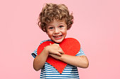 Little curly boy holding heart application and laughing at camera on pink background.