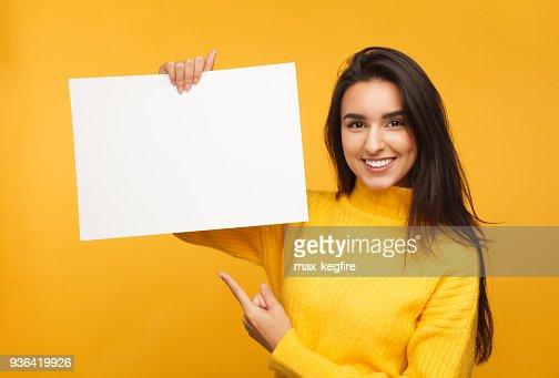 Charmante brunette pointant sur papier blanc : Photo