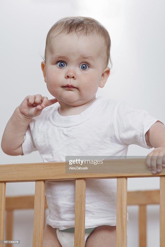 Encantador bebé en una cuna : Foto de stock