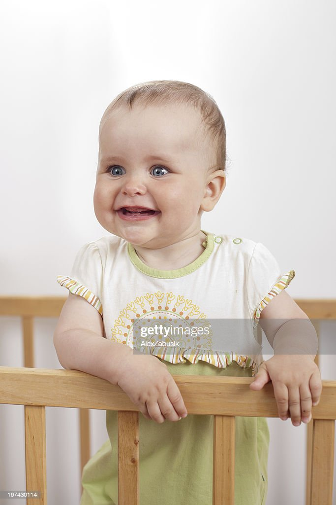 Charming child in the crib : Stock Photo