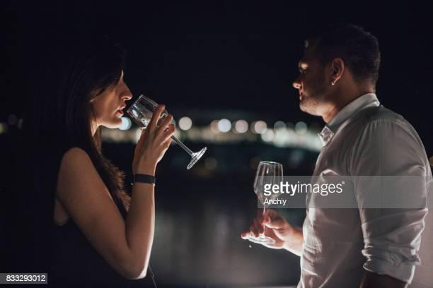 Couple charmant, boire du vin sur le balcon