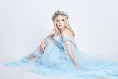Charming fairy woman in a blue ethereal dress and a wreath on her head on white background, gentle mysterious blonde girl with perfect skin and makeup. Cleanliness, body care and skin