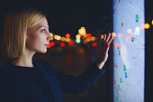 Young female tourist using smart city gadget to get direction in Barcelona central, female in night city standing front big digital screen with city map routes and locations shown on it,filtered image