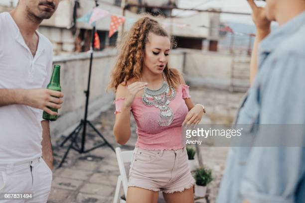 Charming girl dancing on the party on the roof