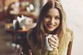 charming girl drinking cappuccino and eating cheesecake in coffee shop