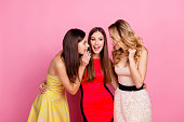 Charming girl holding hand near mouth telling interesting gossips to her pretty friends who laughing, enjoying while standing over pink background, women's day, 8-march