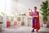 Charming little helper. Cute little child girl makes cleaning the house. Girl is dressed in a Superman costume.