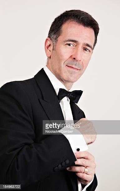 Charming mature gentleman adjusting his tuxedo sleeve
