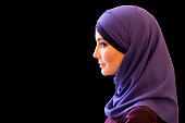 charming Muslim woman in a scarf on her head in profile, black background