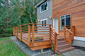 Charming newly renovated home exterior, natural wood siding and grey siding create a beautiful curb appeal. Detail view of a nice walk out deck with wooden handrails.