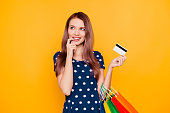 Charming pretty attractive sexy girl having bank card in hand and finger near lips, thinking about buys, what she need and want, standing over yellow background
