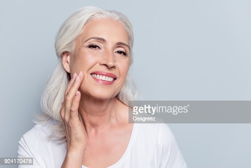 Charming, pretty, old woman touching her perfect soft face skin with fingers, smiling at camera over gray background, using day, night face cream, cosmetology procedures : Foto stock
