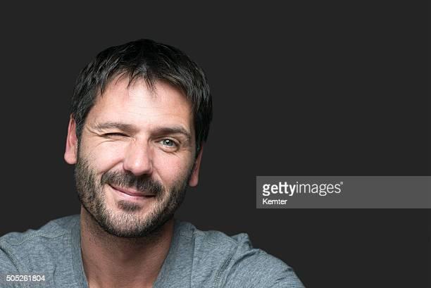 Encantador sorridente homem com piscar de olho para a câmara