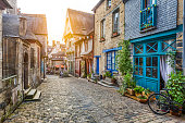 Panoramic view of a charming street scene in an old town in Europe in beautiful evening light at sunset with retro vintage Instagram style pastel toned filter and lens flare sunlight effect in summer