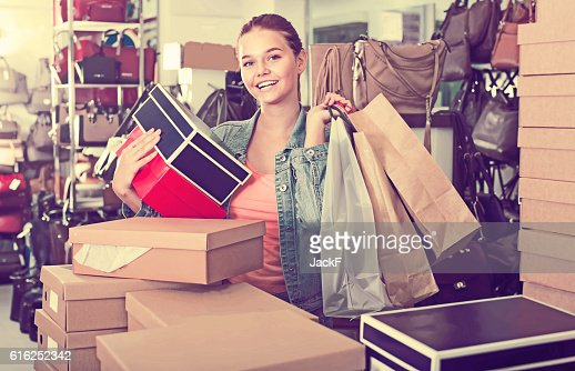 Charming teenager girl holding boxes in shoes boutique : Foto de stock