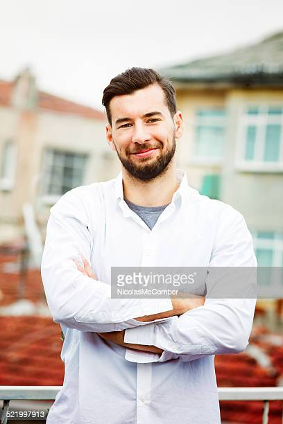 Charming Turkish man portrait on rooftop arms crossed