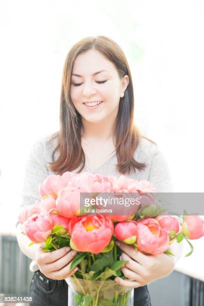 Charming woman embracing flowers in vase