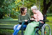 charming young and senior woman have a talk in park