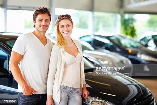 Affascinante giovane coppia standing in auto nuova nello showroom