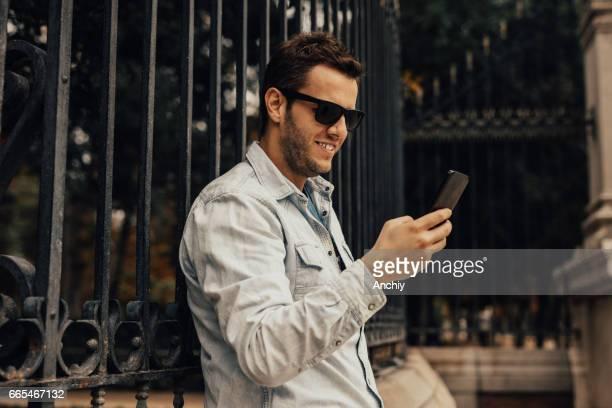 Charmant jeune homme est adossée sur la clôture et il est textos un message sur le téléphone