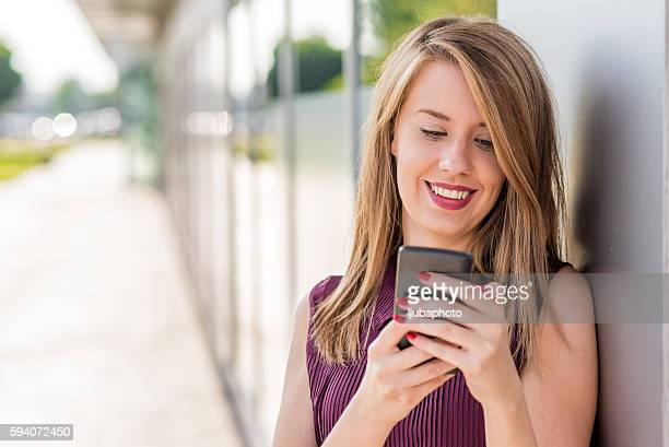 Charming young woman reads message to mobile phone