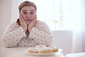 Donuts on the plate. Perplexed chubby woman restraining herself while sitting next to delicious plate of donuts