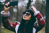 Portrait of stylish black-haired narcissist girl,dressed in spring coat in sunglasses,making a selfie with her smartphone.Natural backgrounds.Close up.