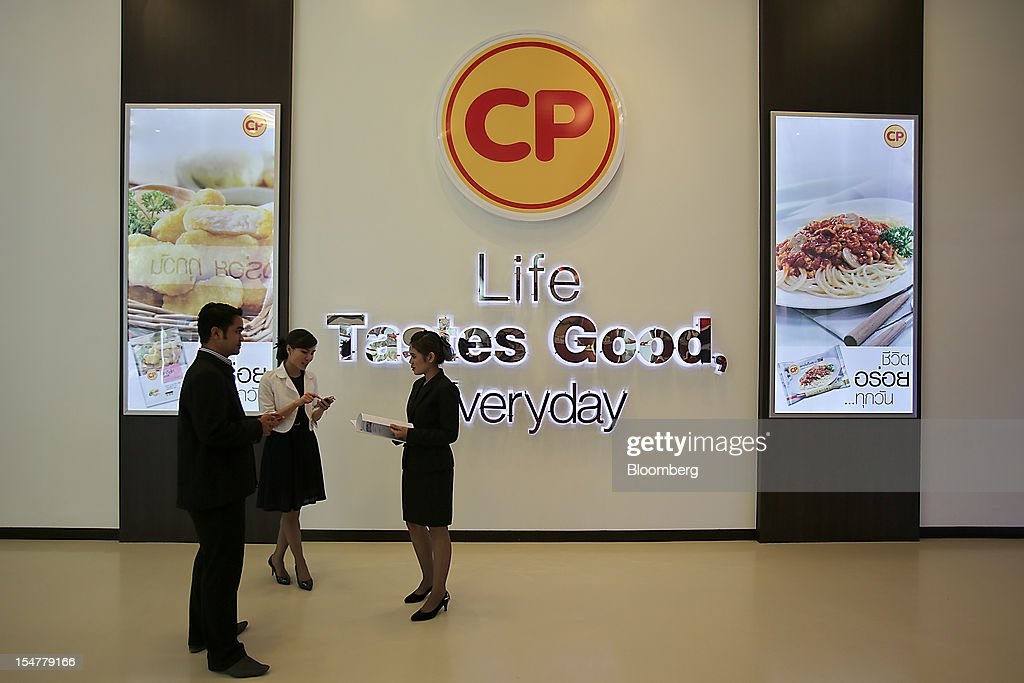 Charoen Pokphand Foods Pcl (CP Foods) employees talk in front of signage displayed at the company's plant in Chok Chai, Nakhon Ratchasima province, Thailand, on Thursday, Oct. 25, 2012. CP Foods, controlled by billionaire Dhanin Chearavanont, is the nation's biggest meat and animal-feed producer. Photographer: Dario Pignatelli/Bloomberg via Getty Images