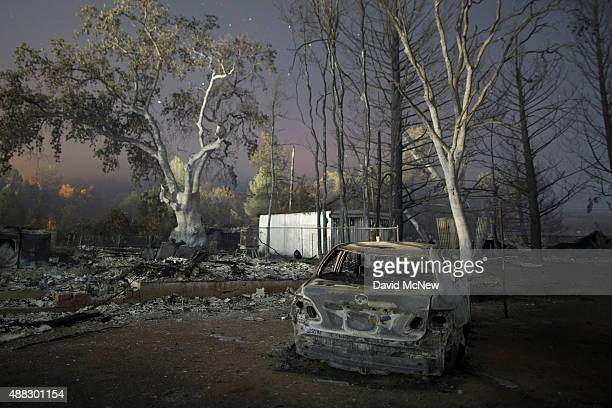 A charred car stands with the ruins of a home that burned in the Valley Fire are seen on September 15 2015 in Middletown California The 104squaremile...
