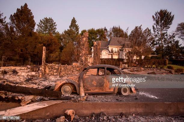 TOPSHOT Charred property is seen before a home that was untouched by the fire in Santa Rosa California on October 15 2017 The death toll from...