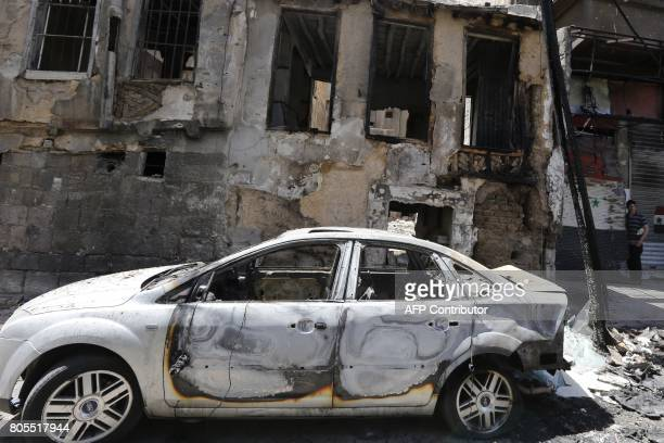 A charred vehicle is seen on the site of a suicide bomb attack in the Syrian capital's eastern Tahrir Square district on July 2 2017 Syrian state...