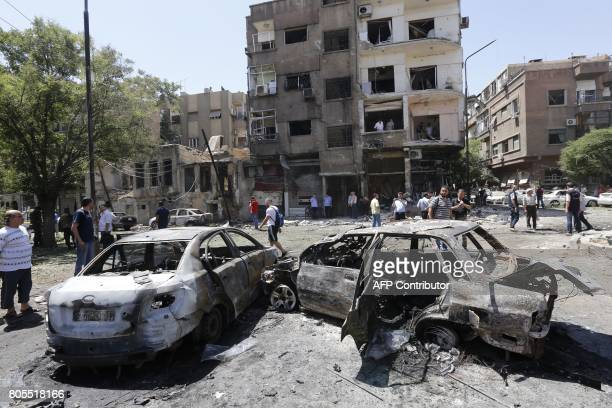 Charred vehicles are seen on the site of a suicide bomb attack in the Syrian capital's eastern Tahrir Square district on July 2 2017 Syrian state...