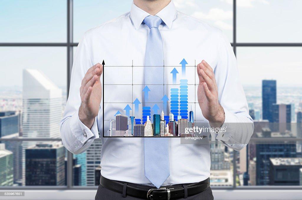 chart and skyscraper in hand : Stock Photo