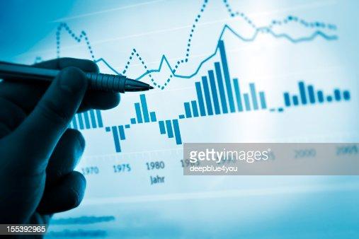Mano señalando con lápiz en un gráfico de ordenador/documento