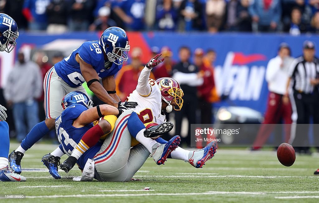 Chase Blackburn of the New York Giants forces a fumble late in the game against Santana Moss of the Washington Redskins at MetLife Stadium on October...