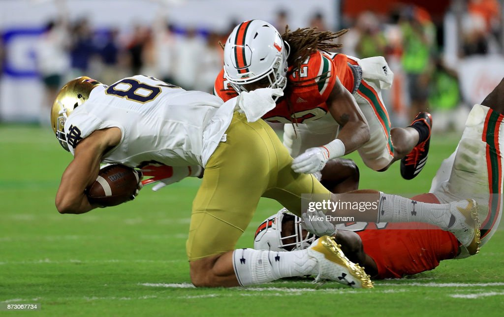 Chase Claypool #83 of the Notre Dame Fighting Irish is tackled by Sheldrick Redwine #22 of the Miami Hurricanes during a game at Hard Rock Stadium on November 11, 2017 in Miami Gardens, Florida.