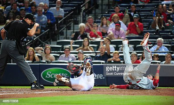 Chase d'Arnaud of the Philadelphia Phillies is tagged out at home by Christian Bethancourt of the Atlanta Braves during the seventh inning at Turner...