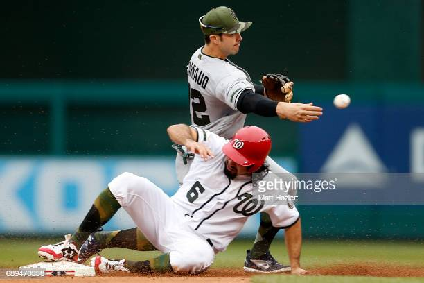 Chase d'Arnaud of the San Diego Padres attempts to turn a double play over Anthony Rendon of the Washington Nationals for the second out of the...