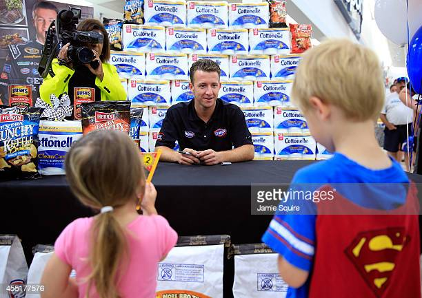Chase Driver AJ Allmendinger talks with young fans while making an appearance at a HyVee grocery store on September 10 2014 in Shawnee Kansas